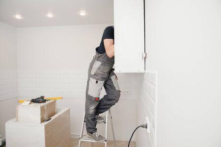 Worker assembling furniture cabinet hinge. Kitchen installation man.