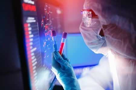 Analysis number of infected people in China and world from virus, doctor in protective chemical suit with respirator computer in laboratory