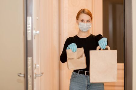 Food delivery and shopping during coronavirus pandemic. Girl holds cardboard boxes in gloves and medical mask 写真素材