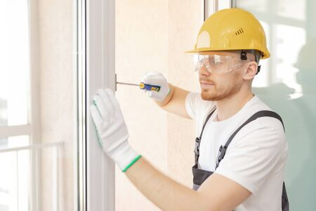 Worker in installing rubber seals on plastic upvc window