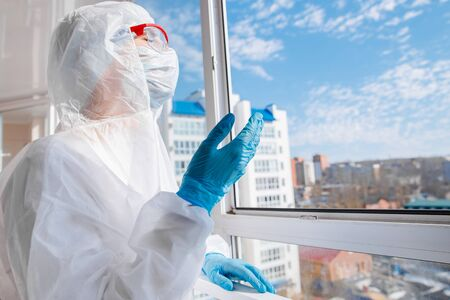 Woman in biohazard medical mask on self isolation quarantine breathes fresh air on balcony with open window