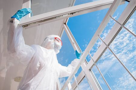 Tired doctor biohazard after hard shift in hospital, coronavirus looks at blue sky
