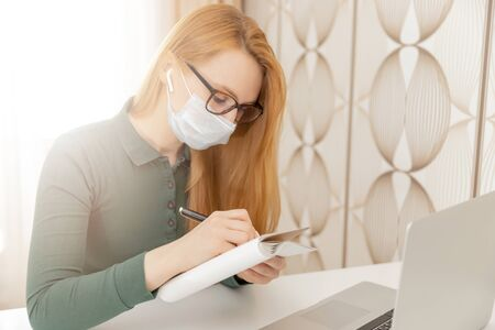 Girl student freelancer in medical mask works computer online from home
