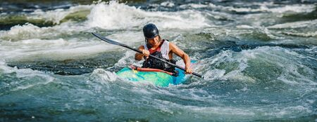 Guy in kayak sails mountain river. Whitewater kayaking, extreme sport rafting