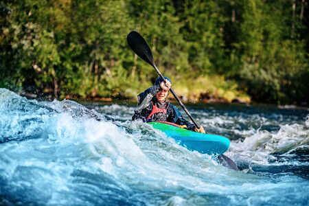 Extreme sport rafting whitewater kayaking. Guy in kayak sails mountain river
