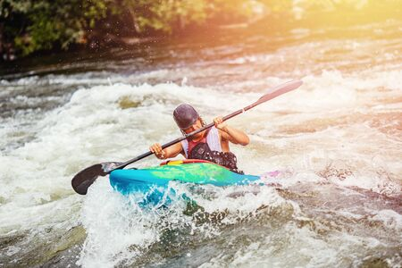 Guy in kayak boat overcomes threshold of mountain river, boiling water. Rafting concept Stock Photo