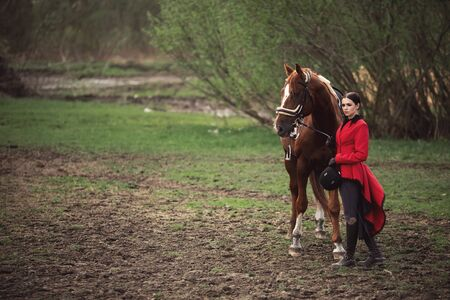Young woman jockey is riding brown horse, Equestrian sport