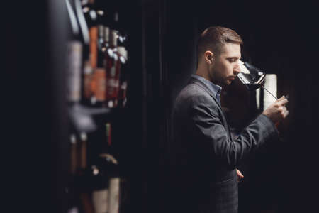Winemaker sommelier man sniffing aroma red wine in glass Imagens
