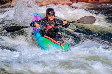 Guy in kayak sails mountain river. Whitewater kayaking, extreme sport rafting Stockfoto