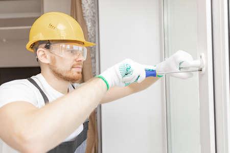 Worker in installing white plastic upvc window on house Stock fotó