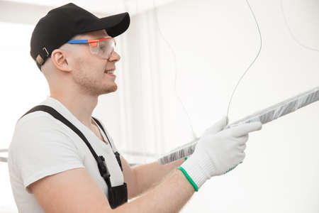 Electrician worker man assembling electric lamps in new apartment