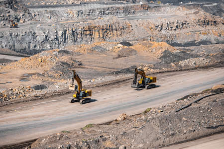Concept open pit mine industry. Metaphor giraffes excavator moving end of working day