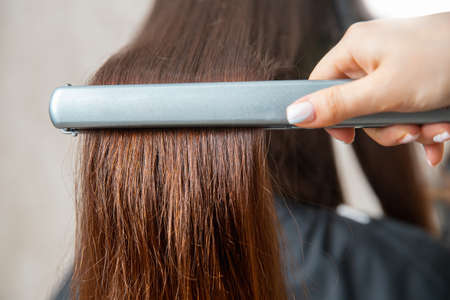 Close up hands of professional hairdresser beauty salon, straighteners curling female hair