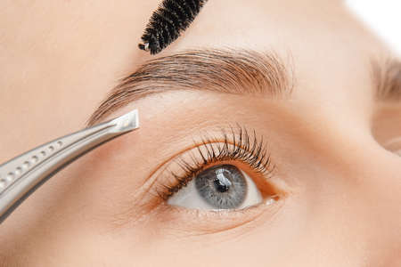 Master tweezers depilation of eyebrow hair in women, brow correction