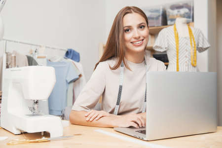Smiling woman seamstress fashion designer working on laptop, accepting orders for sewing clothes. Concept love of work