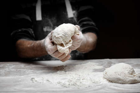 Hands baker preparing yeast dough with white dust flour on black background, scoop for pasta and pizza.