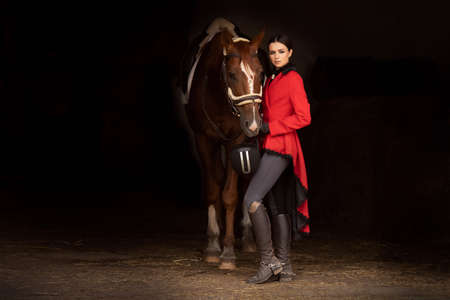 Smiling jockey woman standing with brown horse in stable, black background