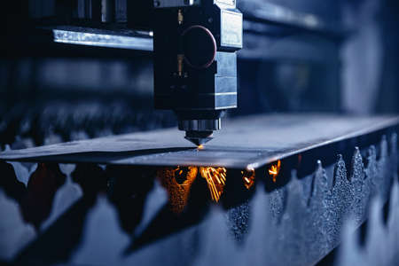 CNC laser machine cutting sheet metal with light spark. Technology plasma industrial, Blue steel color