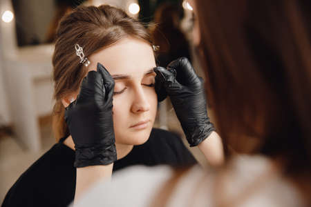 Correction and tinting eyebrows, master applies thread to woman on brow