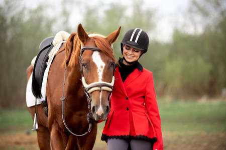 Equestrian sport Woman smile jockey holding horse by bridle outdoors