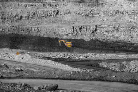 Open pit mine industry work of large yellow excavator for loading and coal mining