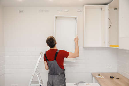 Kitchen installation, worker assembling furniture white carved cabinet front 写真素材