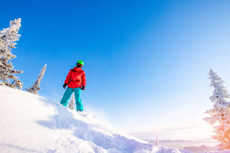 Snowboarder jumping through air with deep blue sky in background, Freeride winter forest