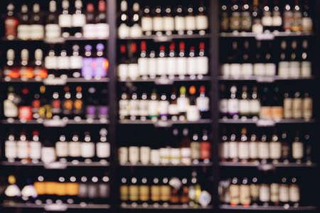 Many glass wine bottles on shelves interior in restaurant. Blurred background