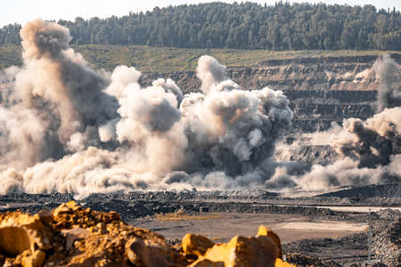 Explosive works on open pit coal mine industry with dust and puffs of smoke Foto de archivo