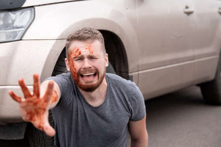 Car accident, man sits with bloodied head near wheel, screaming and crying Stock fotó - 155423024