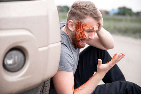 Young man sits with bloodied head near wheel of car, screaming and regretting act Stock fotó - 155423184