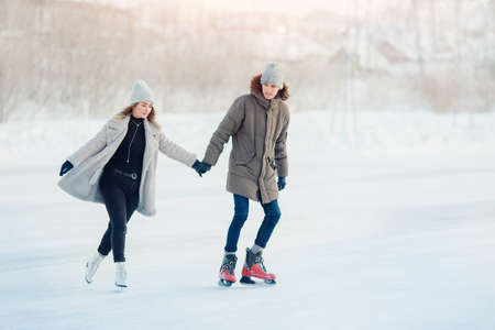 Ice skating lover couple having fun on snow winter holidays