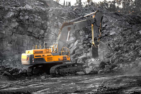 Excavator work loading of coal into Yellow mining truck. Open pit mine industry
