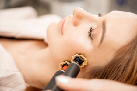 Woman getting face skin care rejuvenation with rf lifting electric apparatus professional beauty salon