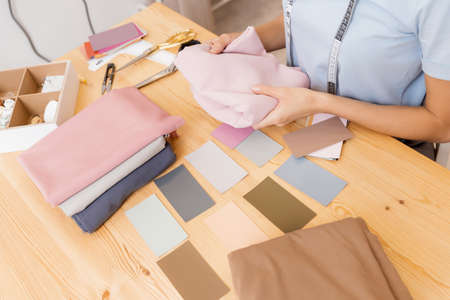 Female designer dressmaker Working on sewing machine in studio. Forms color palette for tailoring fashion clothes