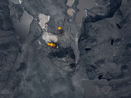 Transporting coal on yellow large dump truck. Open pit mine industry Top aerial view