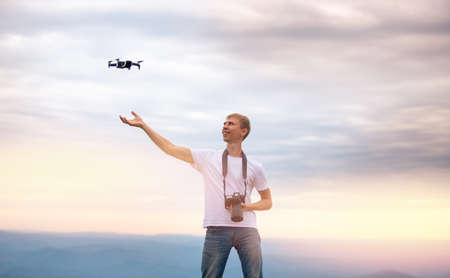 Happy man Photographer with camera controls drone, carries out quadcopter landing on hand, sunset