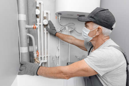 Male plumber in medical mask checks pipes for central hot and cold water supply of apartment