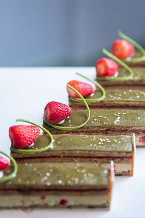 Close-up of pistachio chocolate dessert with strawberries and nuts, catering table setting