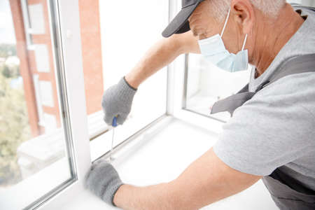 Worker man installs plastic windows and doors with double-glazed white Stock fotó