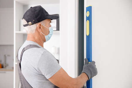 Checking doorway for verticality using bubble level by master carpenter wearing medical mask