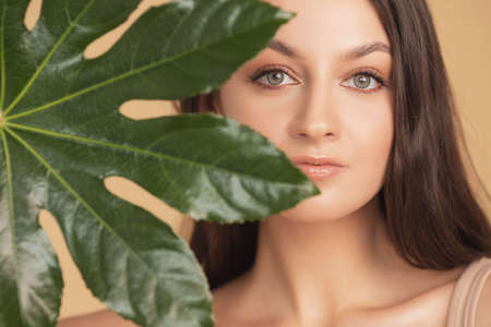 Concept skincare natural flora cosmetics. Beautiful woman with smooth skin in tropical leaves in studio