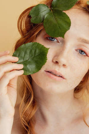 Beautiful young woman redhead blue eyes with green leaves on face. Nature organic cosmetics and makeup