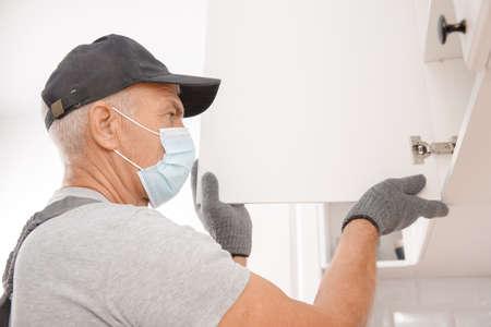 Kitchen installation, worker in medical mask assembling furniture white carved cabinet front