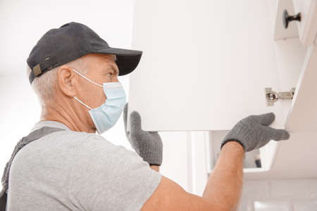 Kitchen installation, worker in medical mask assembling furniture white carved cabinet front
