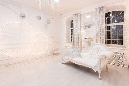 Interior Christmas room silver retro sofa white in light illuminations Фото со стока