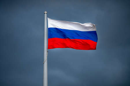 Russia flag waving on blue storm clouds sky background. Concept change power and president, revolution of country