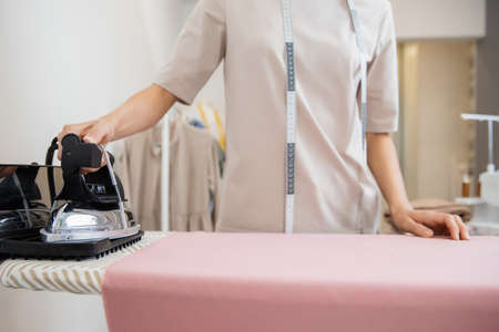Seamstress woman steams iron cloth for sewing clothes