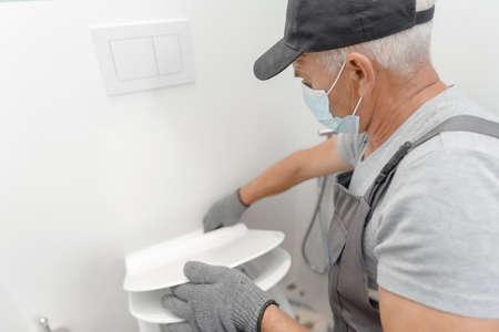 Plumber in medical mask installing toilet bowl in restroom, work in bathroom