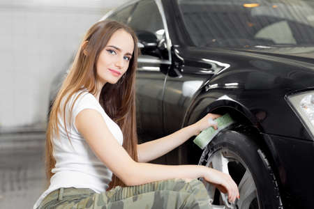 Car wash, girl worker clean tire and rubber wheel with sponge